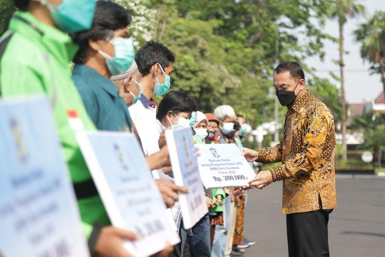Wali Kota Surabaya Eri Cahyadi secara simbolis menyerahkan bansos JPS masing-masing senilai Rp200 ribu kepada 15 MBR di halaman Balai Kota Surabaya, Jumat (10/9/2021).