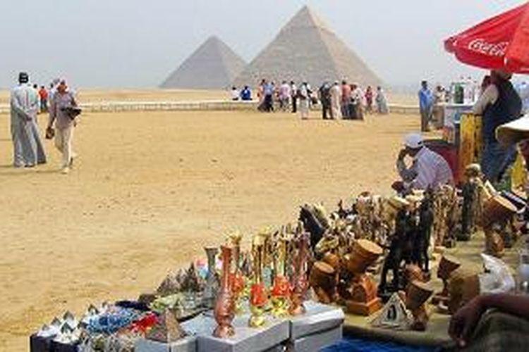 Para penjual suvenir termangu menunggu pembeli di kompleks Piramida Besar Giza di Giza, Mesir, Selasa (21/10/2014). Piramida Besar Giza yang berusia hampir 5.000 tahun masih menjadi ikon pariwisata Mesir paling terkenal di seluruh dunia.