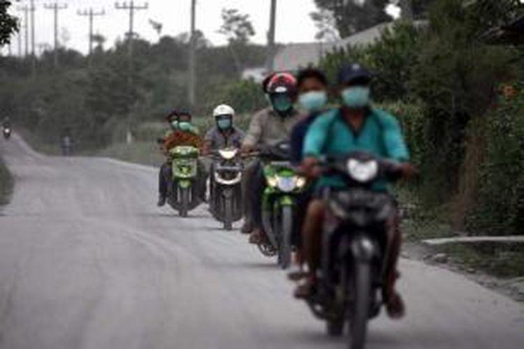 Warga mengenakan masker keluar dari desa di kaki Gunung Sinabung  di Kabupaten Karo, Sumut, Minggu (15/9/2013).  Letusan gunung yang terjadi Minggu pukul 02.51, mengakibatkan ribuan orang dari belasan desa di kaki gunung terpaksa diungsikan.