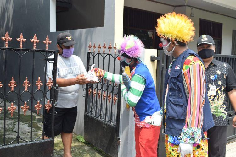 Komunitas Badut bersama PMI Kota Tangerang membagikan masker gratis kepada warga, Kamis (16/4/2020)