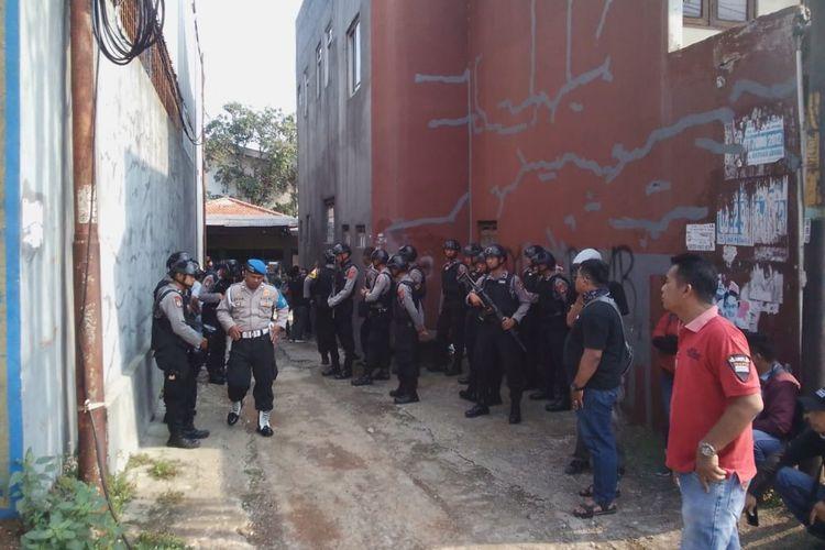 Sejumlah petugas polisi nampak berjaga-jaga di lokasi penangkapan Endang alias Abu Rafi (51) yang diduga sebagai pengikut jaringan ISIS di  Jalan Raya Bogor, Kelurahan Nanggewer, Kabupaten Cibinong, Sabtu (18/5/2019).