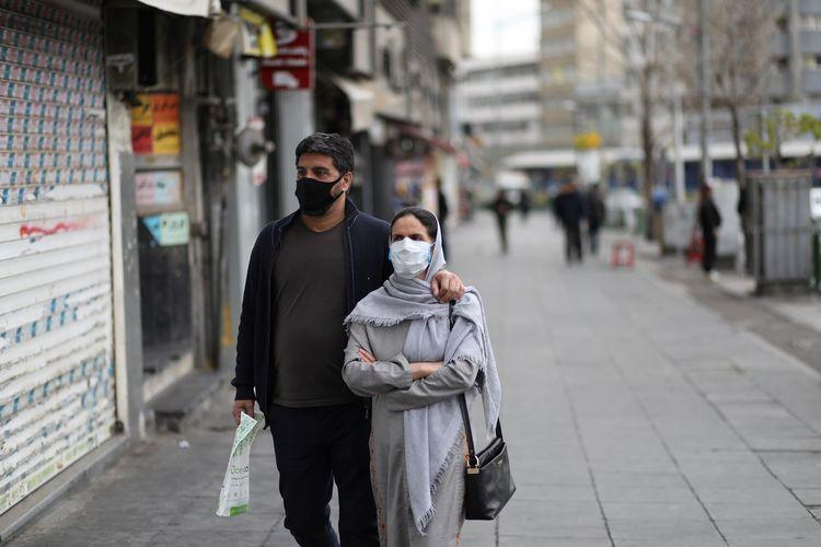 Sepasang warga Iran berjalan mengenakan masker di Enghelab Square, Teheran, Iran, untuk meminimalkan risiko tertular virus corona. Gambar diambil pada 26 Maret 2020.