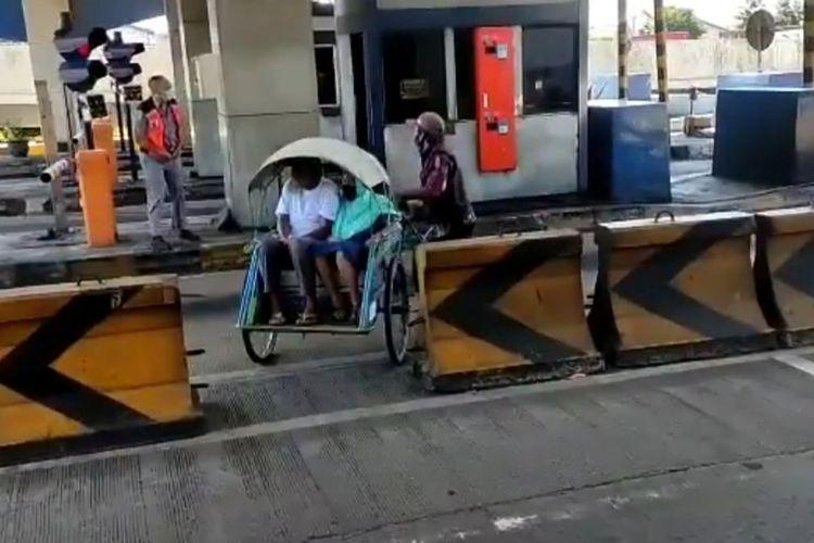 Seorang pria tengah mengayuh becak dengan membawa dua orang penumpang masuk tol Surabaya-Gresik pada Jumat (14/5/2021).