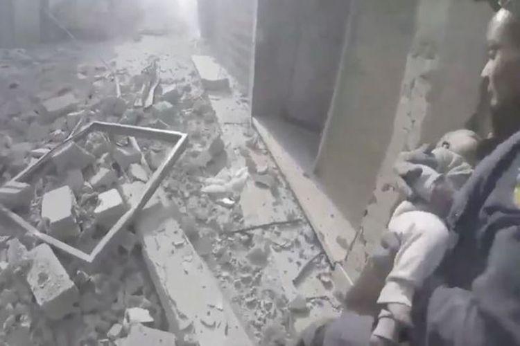 Petugas penyelamat dari Pertahanan Sipil Suriah berusaha mengevakuasi seorang bayi yang ditemukan masih hidup di dalam reruntuhan di Ghouta Timur.