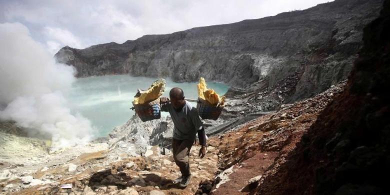 Marzuki, seorang petambang berjalan membawa bakul penuh bongkahan belerang, saat naik dari kawah Gunung Ijen di Banyuwangi, Jawa Timur, Sabtu (16/4/2016). Demi mendapat penghasilan yang terbilang minim, petambang harus menapaki gunung dengan memanggul puluhan kilogram bongkahan belerang di tengah asap beracun.