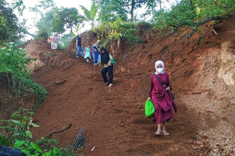 Sejumlah penyintas bencana yang akan mengikuti vaksinasi Covid-19 melintasi jalan setapak di atas longsoran Dusun Ciherang, Nyalindung, Sukabumi, Jawa Barat, Jumat (18/6/2021).