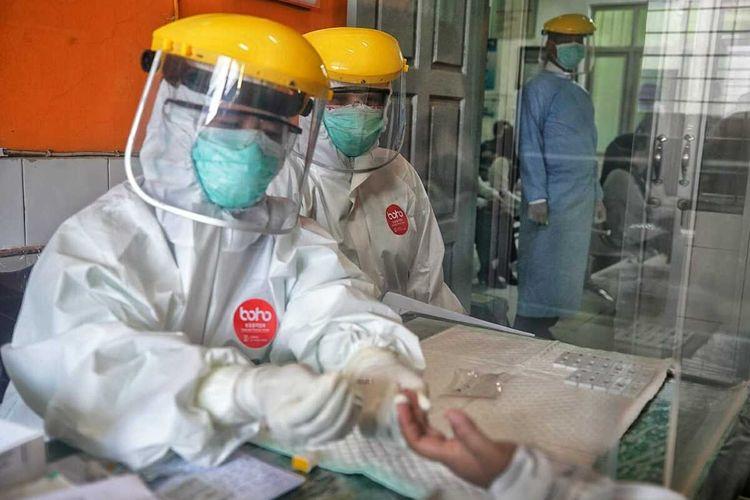 Petugas puskesmas nampak mengambil sampel darah seorang tenaga pendidikan di Kota Madiun untuk dilakukan rapid test Covid-19.