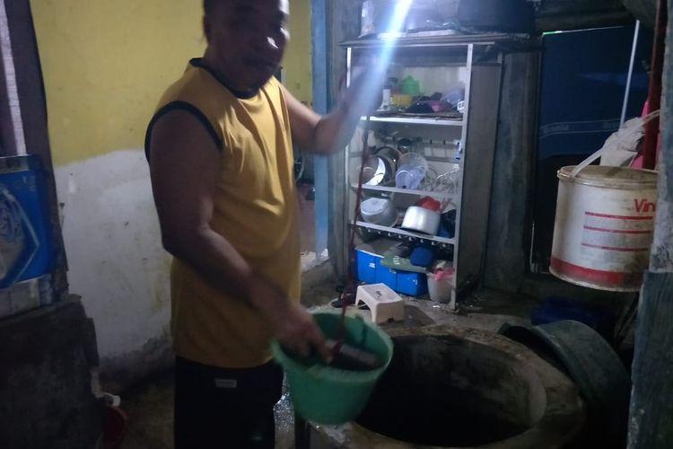 Iyus (53) Warga Sunter Agung saat menimba air sumur yang berada di drpan rumahnya, di Jalan Ancol Selatan, RT 07 RW 03, Sunter Agung, Tanjung Priok, Jakarta Utara, Senin (11/10/2021).