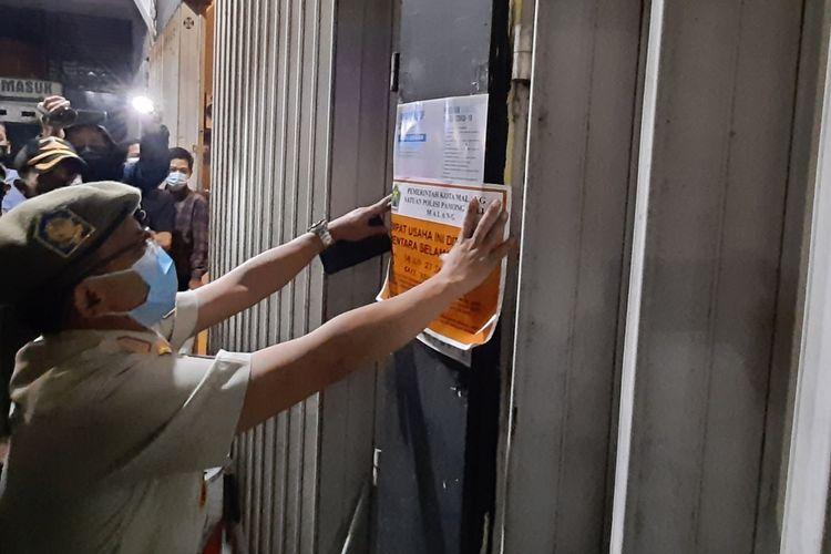 Salah satu petugas Satpol PP Kota Malang saat menutup sementara kafe di Jalan Sigura-Gura karena melanggar jam malam PPKM, Jumat (15/1/2021) malam