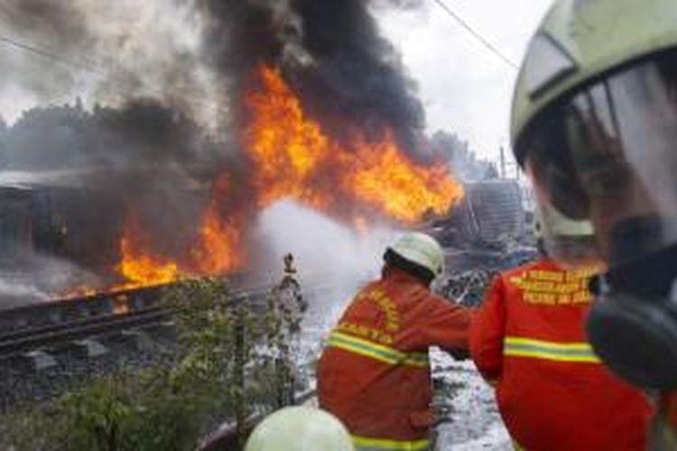 Suasana di lokasi tabrakan kereta rel listrik (KRL) jurusan Serpong-Tanah Abang dengan truk tangki pengangkut bahan bakar di pelintasan Pondok Betung, Bintaro, Jakarta Selatan, Senin (9/12/2013). Kecelakaan mengakibatkan sejumlah rangkaian gerbong dan truk tangki terbakar, menyebabkan seorang masinis dan seorang penumpang tewas, serta puluhan orang mengalami luka bakar.
