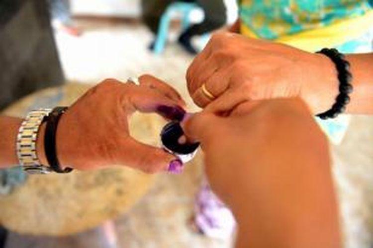 Petugas mencelupkan jari pemilih seusai memberikan suara di tempat pemungutan suara di Kuta, Bali, 9 Desember 2015. 100 juta pemilih hari ini memberikan suara untuk pemilihan kepala daerah yang dilakukan serentak di 32 provinsi untuk pertama kalinya.