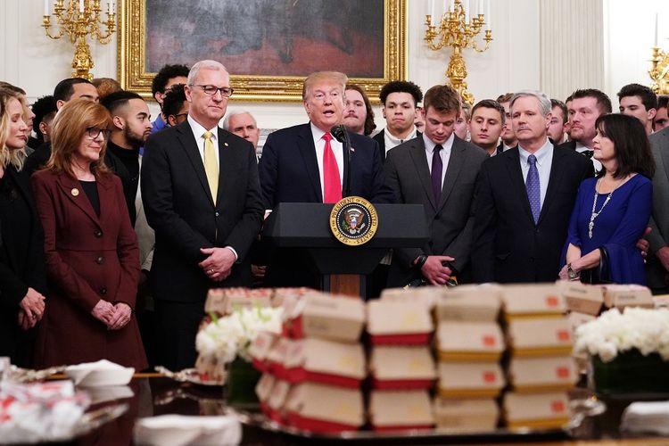 Presiden AS Donald Trump berpidato di depan meja penuh makanan cepat saji ketika menjamu tim American Football North Dakota State Bison yang menjadi juara Division I FCS di Gedung Putih pada 4 Maret 2019.