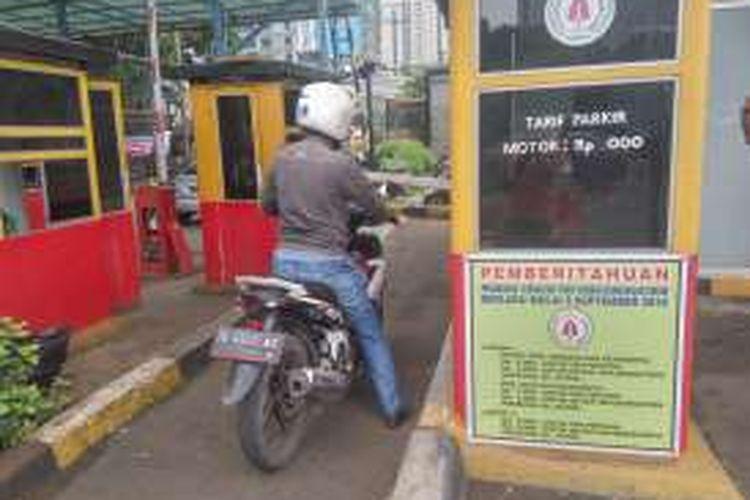 Pengendara sepeda motor saat akan membayar parkir di loket parkir Mapolda Metro Jaya, Jumat (2/9/2016).