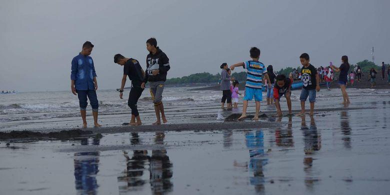 Wisatawan sedang bermain air di Pantai Boom Banyuwangi, Jawa Timur yang berhadapan langsung dengan Selat Bali.