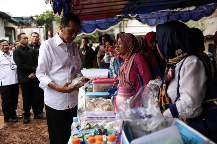 Presiden Joko Widodo membeli kue setelah meninjau kegiatan Pemodalan Nasional Madani alias PNM di Lapangan Bola Perisma, Kelurahan Kalianyar, Kecamatan Tambora, Jakarta Barat, Rabu (8/1/2019). PNM yang akan ditinjau Presiden, yakni PNM Mekaar (Membina Ekonomi Keluarga Sejahtera). PNM Mekaar menekankan pada sisi membantu ibu-ibu prasejahtera menjadi sejahtera dengan cara memberi modal usaha dengan bantuan pelatihan serta pengembangan usahanya lewat bisnis usaha.