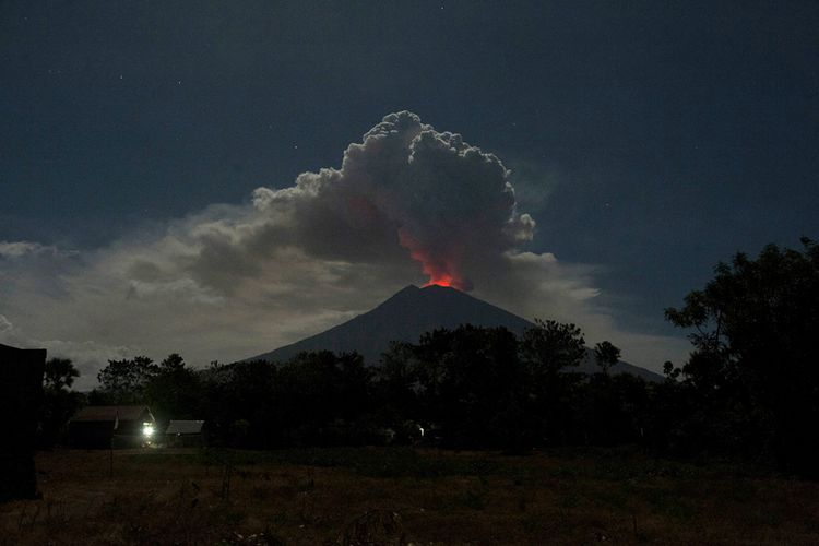Cahaya magma dalam kawah Gunung Agung terpantul pada abu vulkanis terlihat dari Desa Datah, Karangasem, Bali, Jumat (29/6/2018). Pusat Vulkanologi dan Mitigasi Bencana Geologi mencatat terjadinya erupsi Gunung Agung dengan tinggi kolom abu mencapai 2.000 meter namun status gunung tersebut masih pada level siaga.