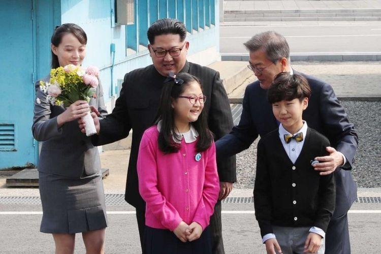 Kim Yo Jong (kiri), saudari dan penasihat pemimpin Korea Utara Kim Jong Un (tengah), membawa buket bunga, saat Presiden Korea Selatan Moon Jae-in (kanan) berpose bersama anak-anak di Panmunjom, Jumat (27/4/2018). (AFP/Korea Summit Press Pool)