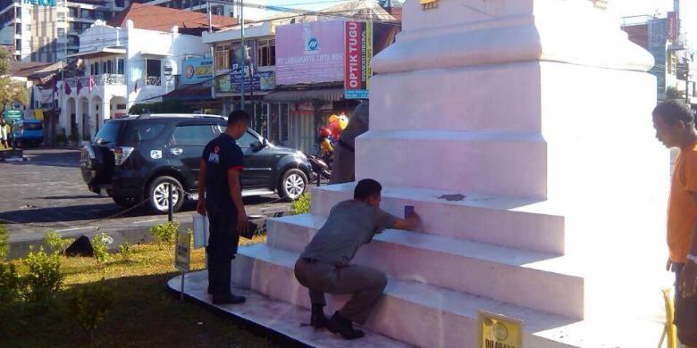 Petugas Pol PP dan pemadam kebakaran saat membersihkan Tugu Yogyakarta dari cat berwarna merah.