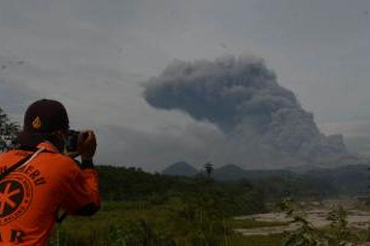 Warga mengamati abu vulkanik yang meninggi keluar dari Gunung Kelud yang terlihat dari jarak lima kilometer di Desa Penataran, Kecamatan Nglegok, Kabupaten Blitar, Jumat (14/2/2014). Menurut Pusat Vulkanologi dan Mitigasi Bencana Geologi (PVMBG), Gunung Kelud yang meletus pada Kamis lalu sekitar pukul 22.30 WIB bersamaan keluarnya tremor tersebut, mengalami 442 kali gempa vulkanik dangkal. SURYA/AHMAD ZAIMUL HAQ