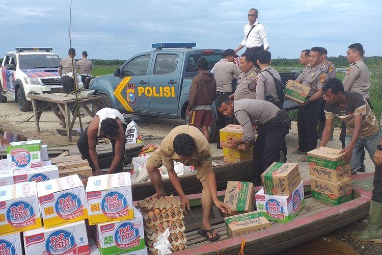 Petugas kepolisian Polres Rohul dan Polsek Bonai Darussalam memuat bantuan sembako ke dalam pompong untuk disalurkan kepada korban banjir di Desa Bonai, Kecamatan Bonai Darussalam, Kabupaten Rohul, Riau, Senin (2/12/2019).