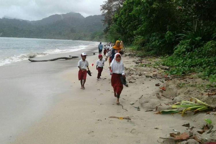 Siswa SD Negeri 11 Seram bagian Timur di Pedalaman Pulau Seram Maluku berjalan menyusuri pantai untuk mengikuti upacara HUT Kemerdekaan RI di Desa Loko, Selasa (17/8/2021)