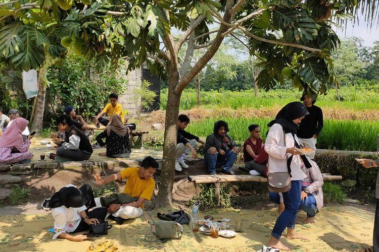 Para pengunjung duduk lesehan di tepi sawah Warung Kopi Klotok, Sleman Yogyakarta, Rabu (22/1/2020). Pengunjung bisa duduk di dalam rumah joglo maupun di luar dengan cara lesehan tikar.