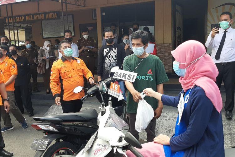 Nani Apriliani Nurjaman (25) Menyerahkan Bungkusan Sate kepada Bandiman saat rekonstruksi di Mapolres Bantul Senin (7/6/2021)