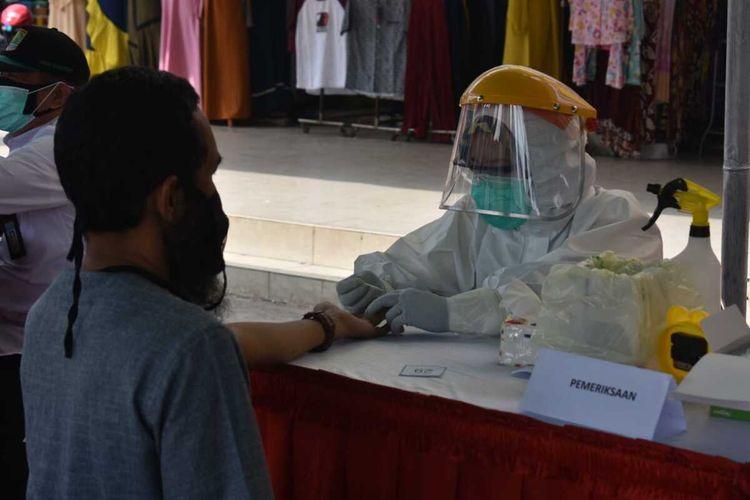Salah seorang pengunjung Pasar Johar Karawang tengah mengikuti rapid test atau tes cepat, Rabu (13/5/2020).