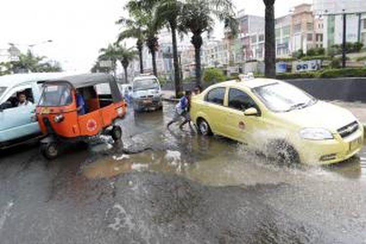 Kondisi jalan berlubang yang terdapat di Jalan Gunung Sahari, Jakarta Utara, Sabtu (1/2/2014). Banjir yang menggenangi Jakarta beberapa waktu lalu membuat sejumlah ruas jalan rusak dan kerap menyebabkan kemacetan dan kecelakaan lalu lintas.