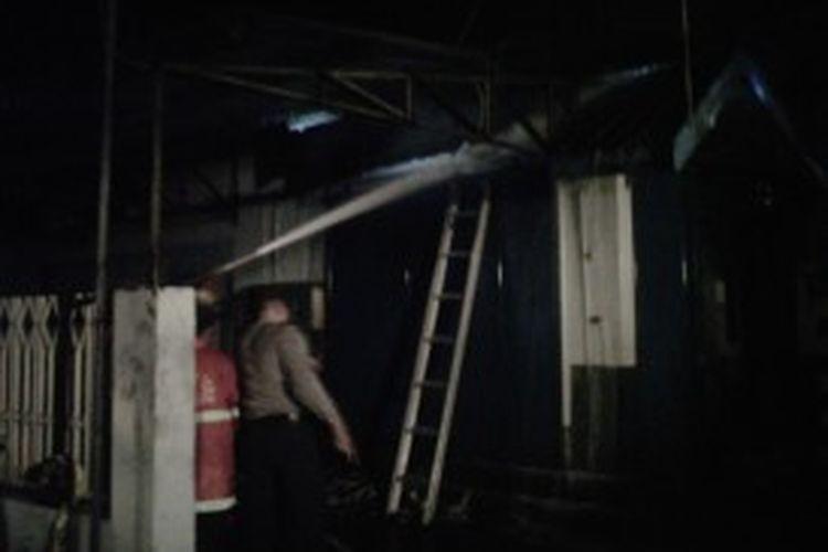 Beberapa petugas berusaha memadamkan api.