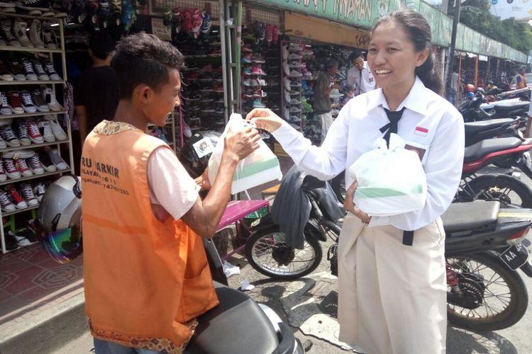 Salah satu siswa SMA Negeri 3 Yogyakarta saat membagikan nasi kotak kepada salah satu tukang parkir di jalan Mataram Kota Yogyakarta