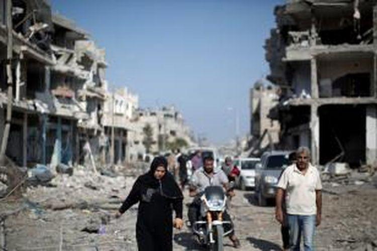 Sejumlah warga Gaza berjalan di tengah reruntuhan bangunan yang hancur akibat serangan Israel. Kedua pihak bertikai sepakat melakukan gencatan senjata selama 72 jam. Namun, baru beberapa jam gencatan senjata berjalan kedua belah pihak sudah saling melepaskan tembakan.