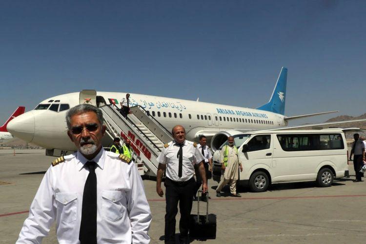 Sekelompok pilot dari maskapai Ariana Afghan tampak berjalan di area Bandara Internasional Hamid Karzai di Kabul, Afghanistan, setelah mendarat pada 5 September 2021.