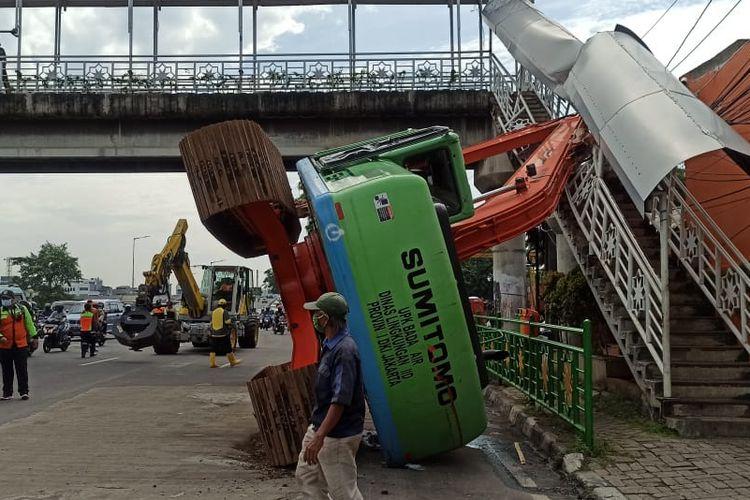 Sebuah alat berat escavator terbalik dan menimpa Jembatan Penyeberangan Orang (JPO) di Jalan Abdullah Syafei di sisi jalan mengarah ke Casablanca, Kebon Baru, Tebet, Jakarta pada Selasa (22/9/2020) pagi.