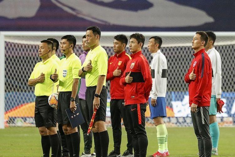 Para pemain dan ofisial pertandingan memberikan penghormatan kepada semua yang terpengaruh pandemi virus corona jelang laga Liga Super China antara Wuhan Zall dan Qingdao Huanghai di Suzhou, Sabtu (25/7/2020).