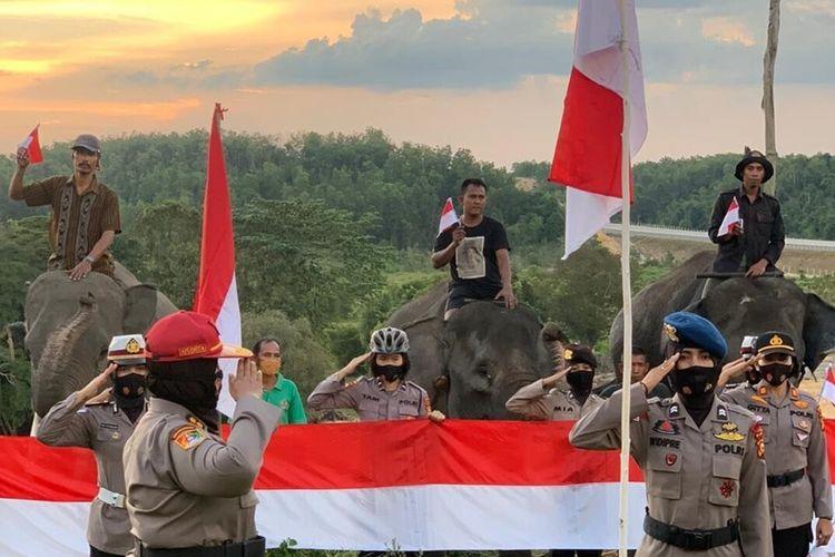 Polwan Polda Riau saat menggelar upacara bendera merah putih pada peringatan HUT ke-75 Republik Indonesia di puncak bukit Kampung Pelatihan Gajah, Kecamatan Minas, Kabupaten Siak, Riau, yang juga diikuti tiga ekor gajah sumatera jinak, Senin (17/8/2020).
