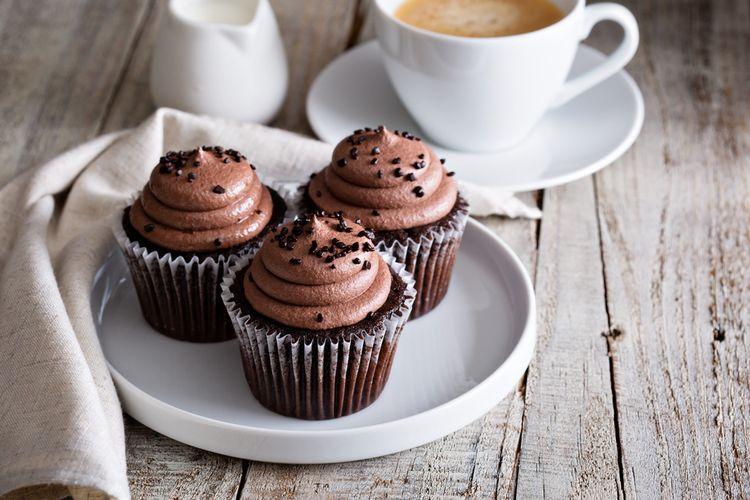 Ilustrasi cupcake cokelat dengan hiasan buttercream cokelat.
