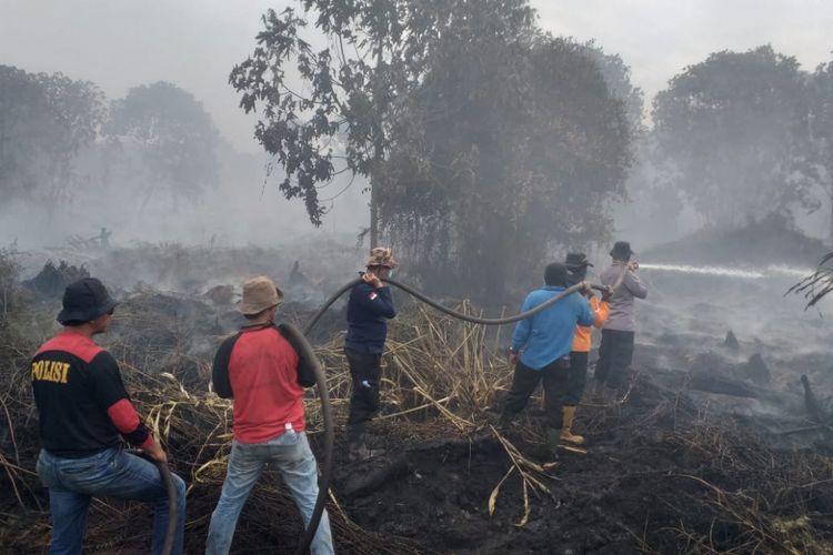 Petugas gabungan memadamkan api kebakaran lahan gambut di lahan PT Sumber Sawit Sejahtera (SSS) di Desa Kuala Panduk, Kecamatan Teluk Meranti, Kabupaten Pelalawan, Riau, Minggu (10/3/2019).