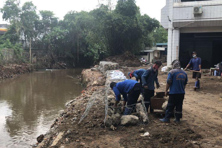 Sejumlah petugas Suku Dinas Sumber Daya Air Jakarta Selatan membangun bronjong berkawat untuk menahan air sementara terkait jebolnya tembok Plaza Bisnis Kemang, Bangka, Mampang Prapatan, Jakarta Selatan pada Rabu (3/3/2021) sore.