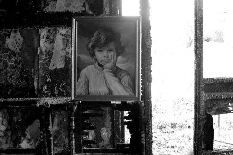 Kutukan lukisan The Crying Boy di antara bangunan yang kebakaran. [Via India Times]