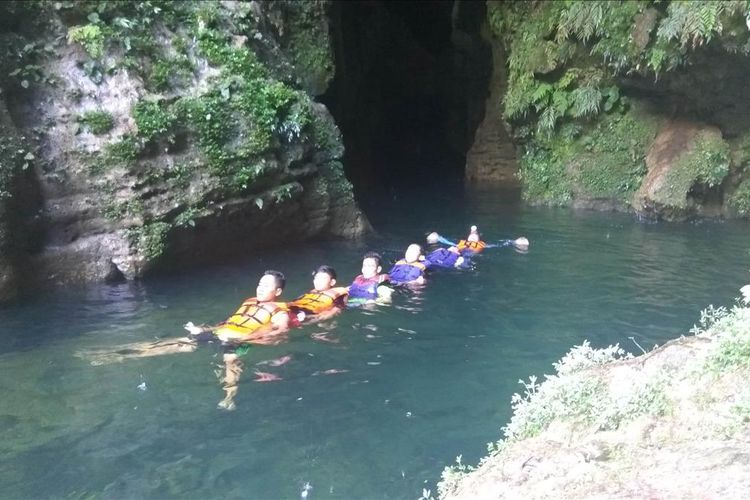 wisatawan asyik bermain body rafting di arus air yang berasal dari dalam gua.