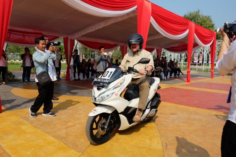 Gubernur Sumatera Selatan Alex Noerdin menjajal Honda PCX saat acara penyerahan 50 unit Honda PCX dari Astra Motor Sumsel kepada panitia penyelenggara Asian Games 2018 Palembang, di Jakabaring Sport City, Senin (23/7/2018). Secara simbolis, penyerahan dilakukan oleh Kepala Wilayah Astra Motor Sumsel, Ronny Asgustinus.