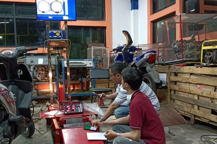 Alvin Rahmad Widyanto bersama rekannya sedang menguji katalitik konverter di knalpot sepeda motor.