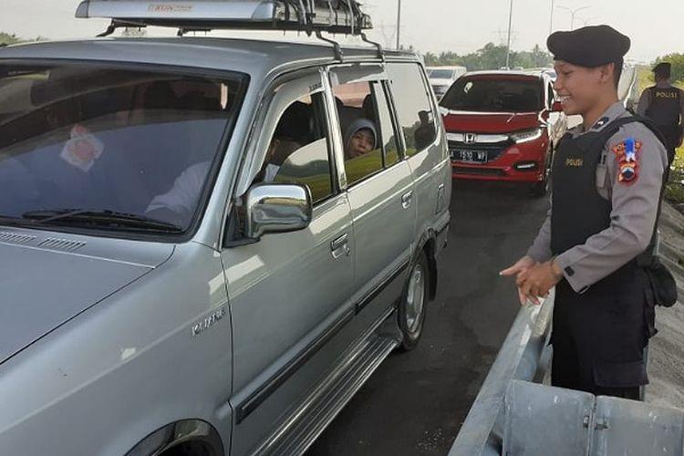 Salah seorang anggota tim sisir tol Polres Pekalongan Jawa Tengah memgingatkan pemudik agar tidak berhenti di bahu jalan.