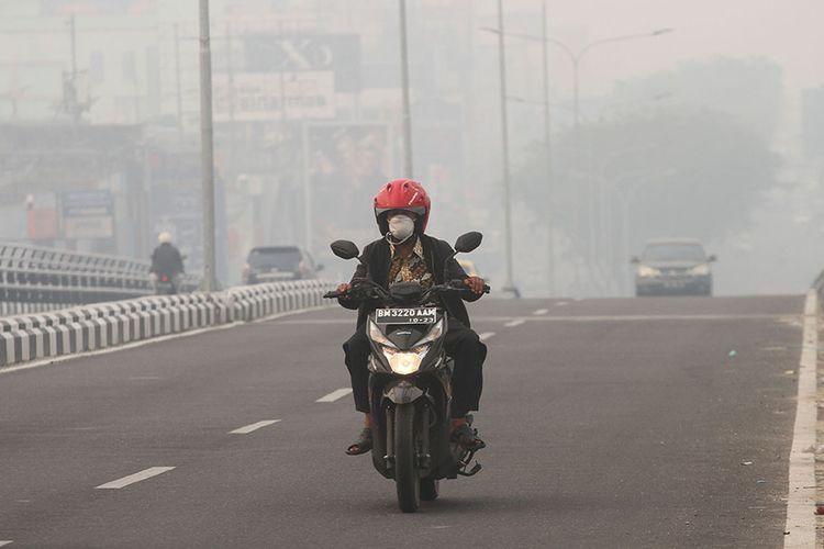 Pengendara sepeda motor menembus kabut asap pekat dampak dari kebakaran hutan dan lahan yang menyelimuti Kota Pekanbaru, Riau, Senin (9/9/2019) pagi. Berdasarkan data Badan Meteorologi Klimatogi dan Geofisika (BMKG) Pekanbaru melalui satelit Terra/Aqua pada Senin (9/9) terpantau 1.278 titik panas di Sumatera.