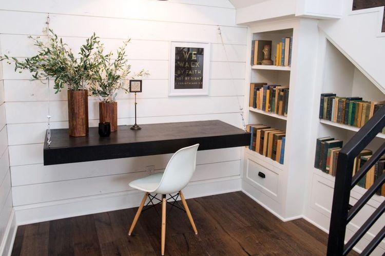 Meja kerja simpel dan rak buku di bawah tangga