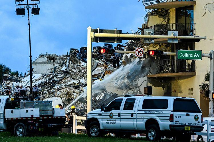 Tim SAR bersama pemadam kebakaran Miami Dade melakukan operasi pencarian di apartemen yang ambruk sebagian di Surfside, Miami, Florida, Amerika Serikat, pada Kamis (24/6/2021). Hingga Jumat pagi (25/6/2021) dilaporkan satu orang tewas dan 99 korban hilang.