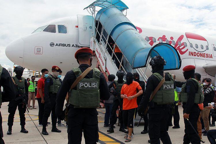 Petugas Detasemen Khusus (Densus) 88 membawa terduga teroris dari Lampung setibanya di Bandara Soekarno Hatta, Tangerang, Banten, Rabu (16/12/2020). Sebanyak 23 orang terduga teroris jaringan Jamaah Islamiyah (JI) yang ditangkap di Lampung dibawa ke Jakarta untuk pemeriksaan lebih lanjut oleh Densus 88.