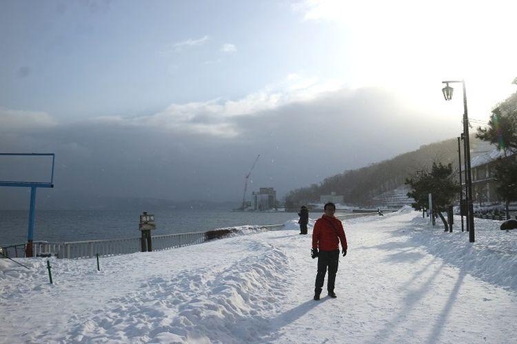 Wisatawan berfoto di tepi Danau Toya, Kota Toyako, Prefektur Hokkaido, Jepang, Selasa (12/2/2019). Danau Toya berlokasi di Kota Toya yang memiliki resort pemandian air panas di sepnajang tepi Danau Toya, di bawah kaki pegunungan Gunung Usu.
