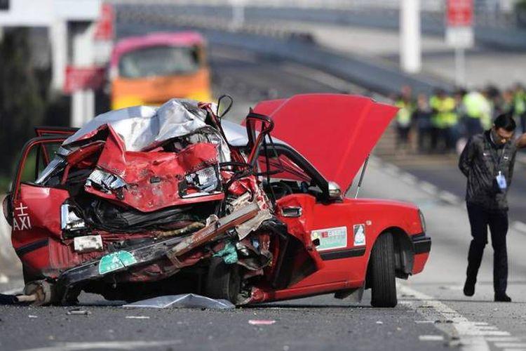 Polisi berada di sekitar taksi yang hancur akibat ditabrak bus di Hong Kong pada Jumat (30/11/2018). (AFP/Anthony Wallace)